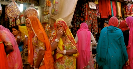 Brightly clad Rajasthani women in the market /bazaar.  Rajasthan desert folk are known for their colorful saris!