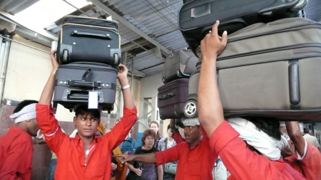 Train employees carrying our luggage onto the train!