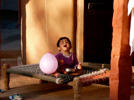 Child at the carpet weaver's home,playing with pink balloon and eating a snack