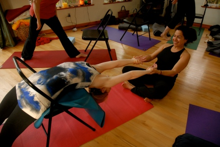 Fran assists Linsey in a backbend using a chair